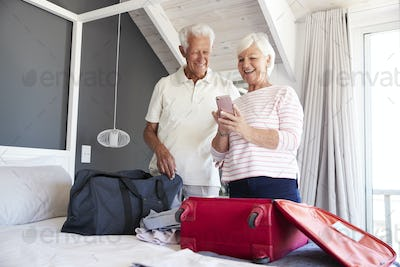 Senior Couple Look At Mobile As They Check In To Vacation Rental