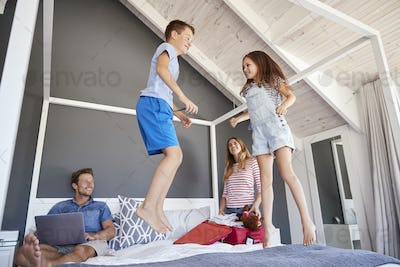 Excited Children Jump On Bed As Parents Pack For Vacation