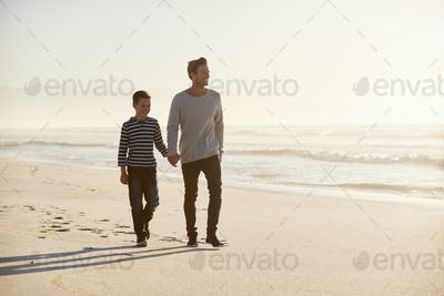 Father And Son Walking Along Winter Beach Hand In Hand