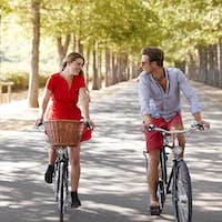 Couple riding bikes on an empty road looking at each other