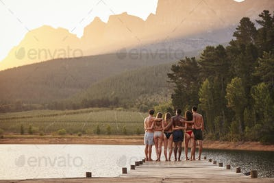 young adult friends standing on a jetty in a lake, back view