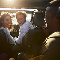 Four young adult friends travelling together in a car