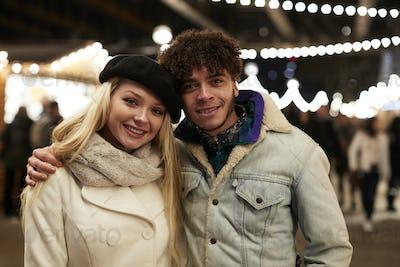 Portrait Of Couple Enjoying Christmas Market At Night