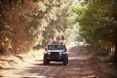 Friends having fun driving in an open top jeep