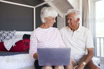 Senior Couple Look At Laptop As They Check In To Vacation Rental
