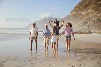 Multi Generation Family On Vacation Walking Along Beach Together