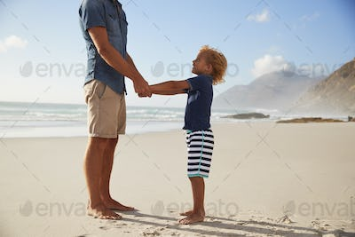 Father Holding Hands With Son On Summer Beach Vacation