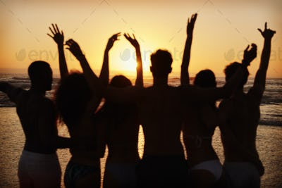 Silhouette Of Friends On Beach Vacation Watching Sunset Over Sea