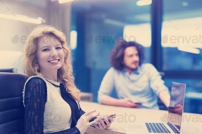 Elegant Woman Using Mobile Phone in startup office building
