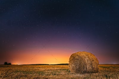 Night Starry Sky Above Field Meadow With Hay Bale After Harvest.