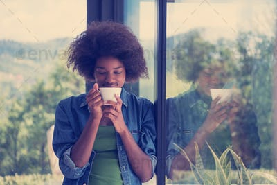 African American woman drinking coffee looking out the window