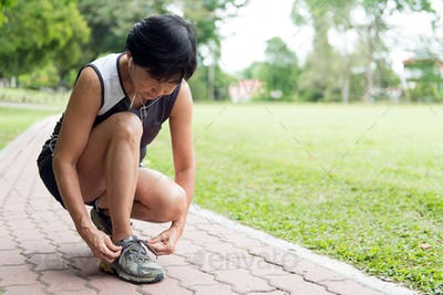 Senior jogger tighten her running shoe laces