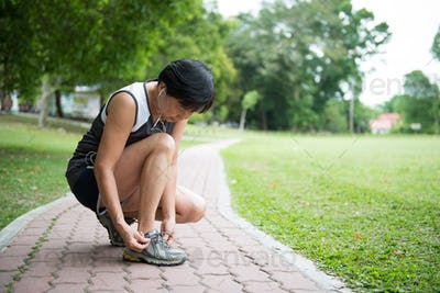 Senior jogger tighten her running shoe laces