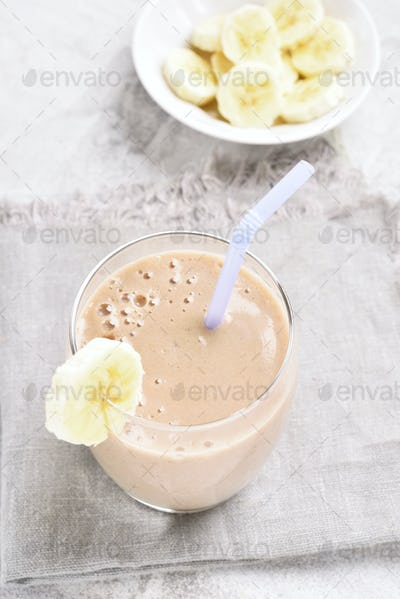Healthy drink milkshake with banana in glass on stone table.