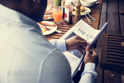 Rear view of black man reading newspaper while having breakfast