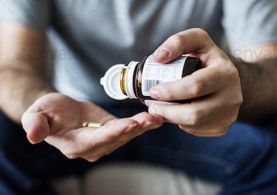 Sick man taking some pills
