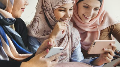 Group of islamic women talking and watching on the phone together