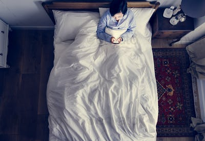 Woman in bed using her cellphone in the dark