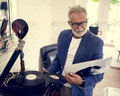 An elderly man playing a record