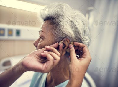 Asian old woman having her ears checked