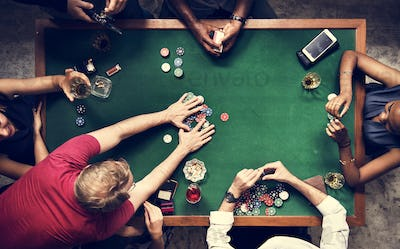 Diverse group playing poker and socialising
