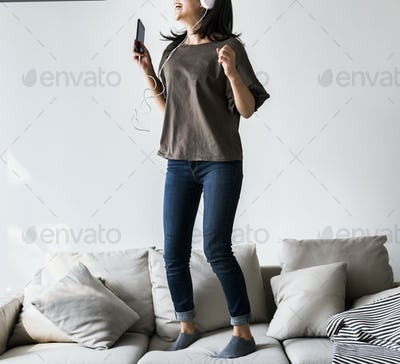 Asian woman enjoying music at home leisure and music concept