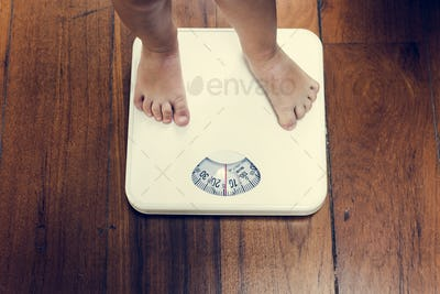 Closeup of kid legs on weight scale
