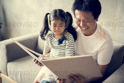 Asian father and daughter reading together