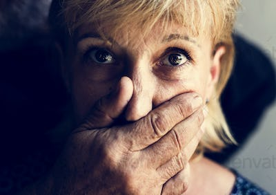 Closeup of caucasian woman with a hand covering her mouth