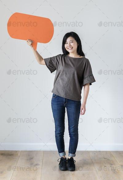 Happy Asian woman holding copyspace speech bubble