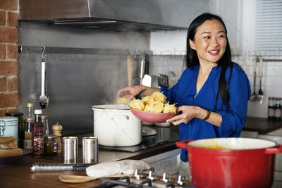 Asian woman cooking pasta in the kitchen