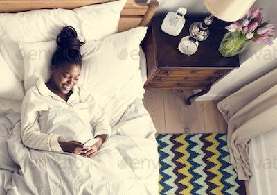 Smiling African American woman on bed using a cellphone