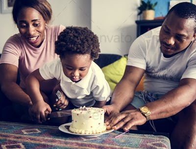 Black family cutting birthday cake