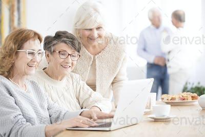 Smiling senior women using laptop