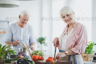 Smiling senior woman cutting tomatoes