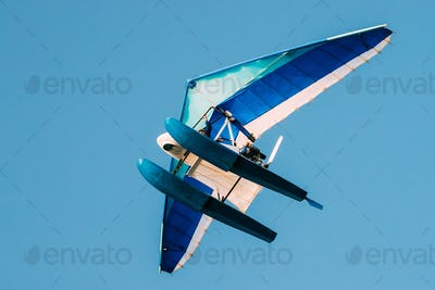 Motorized Hang Glider Flying On Blue Clear Sunny Sky Background
