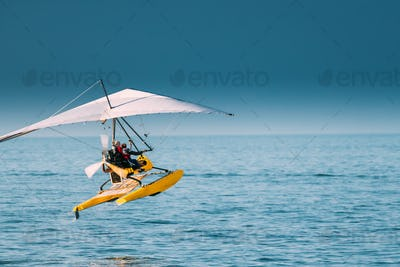 Motorized Hang Glider With Muslim Woman Take Off Frow Sea In Sun