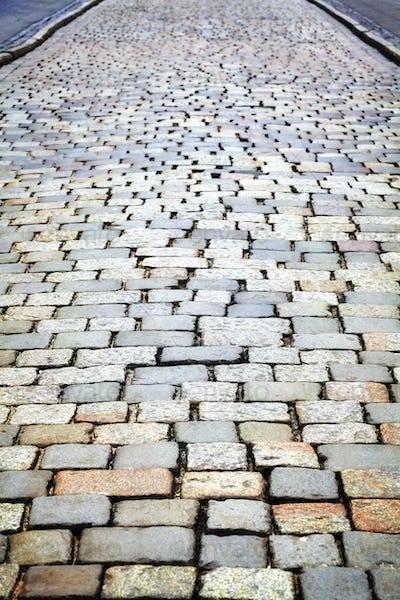 Cobblestone street pavement, urban background.