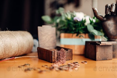 Needlework, metal rings and wooden box on table