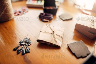 Gift box and handmade earrings on wooden table