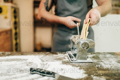 Male chef in apron works with pasta machine