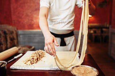 Male chef prepares dough for apple strudel