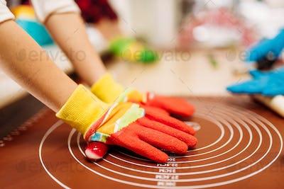Childrens hands in gloves, caramel making