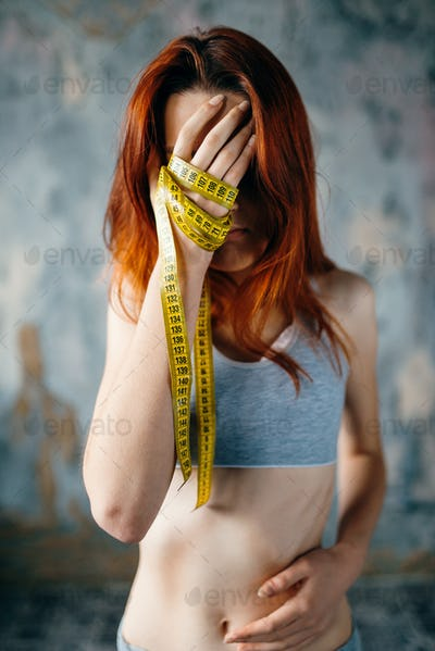Skinny woman, hands tied in measuring tape