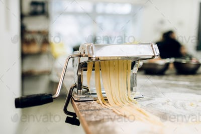 Pasta machine with dough closeup, nobody