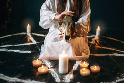 Female person holds skull in hands, magic ritual