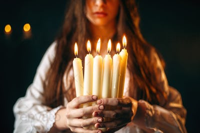 Female person holds candles in hands, divination