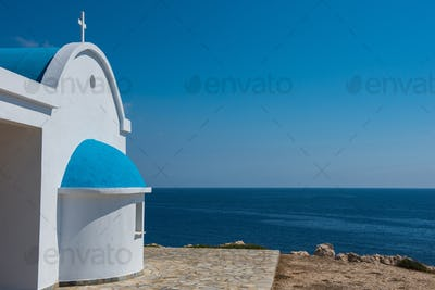 Whitewashed church with blue roof near the sea. Agioi Anargyroi chapel, Cyprus