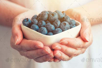 Woman offering blueberry myrtilles