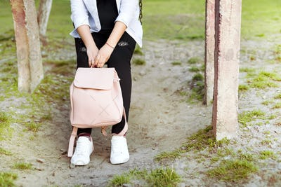 Women's legs in jeans and sneakers, backpack and smart phone